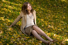 Girl sitting on autumn leaves. The having a rest thoughtful girl on autumn leaves in park Royalty Free Stock Photos