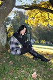 Girl sitting in autumn park Royalty Free Stock Image
