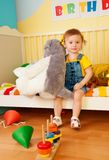 Girl sitting in the baby bed with boys Royalty Free Stock Image