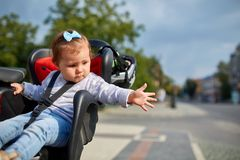 Girl sitting in a baby bike seat of a bicycle of her father safety emotions anxiety kids children parenting. Shot of a little girl sitting in a baby bike seat Stock Images