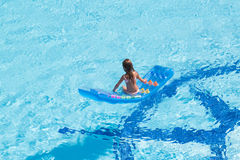 A girl sitting back on mattress in the pool Royalty Free Stock Images