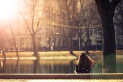 Girl sitting back by the pond royalty free stock image