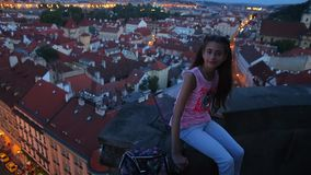 Girl sitting on the background of the night city stock footage
