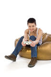 Girl sitting on a bag plays video game. Lovely girl sitting on a bean bag plays video game Royalty Free Stock Photography