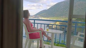 Redhead girl sitting the balcony of hotel and looking to lagoon sea stock video