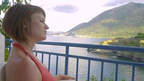 Redhead girl sitting the balcony of hotel and looking to lagoon sea stock video footage