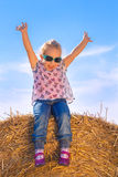 A girl sitting on a bale of straw rising her arms Royalty Free Stock Photo