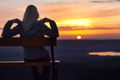 Girl sitting on a banch at sunset Stock Photo
