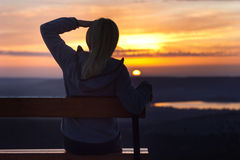 Girl sitting on a banch at sunset Stock Image