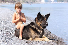 Girl sitting on the bank with a dog Stock Photo