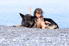 Girl sitting on the bank with a dog Royalty Free Stock Photos
