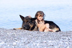 Girl sitting on the bank with a dog Stock Photos