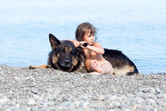 Girl sitting on the bank with a dog Royalty Free Stock Photography