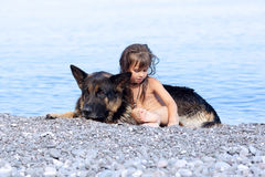 Girl sitting on the bank with a dog Stock Photography