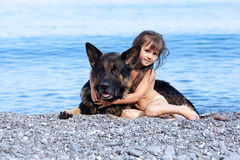 Girl sitting on the bank with a dog Stock Image