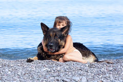 Girl sitting on the bank with a dog Royalty Free Stock Photo