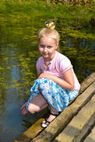 Girl sitting on the bank of a pond. Girl sitting on the bank of the pond with his hand in the water Royalty Free Stock Photography