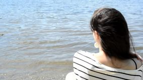 Girl sitting on the bank turns and smiles stock footage