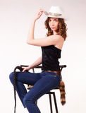 Girl sitting on a bar stool. Girl in a cowboy hat sitting on a bar stool stock photos