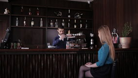 Girl sitting at the bar and waiting for the bartender to prepare a cocktail stock video