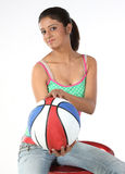 Girl sitting with basket ball Stock Image