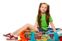 Girl sitting in basket with clothes stock image