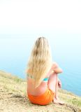 Girl sitting on the beach. Hugging her knees Royalty Free Stock Photos