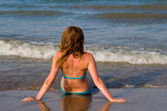 Girl sitting on the beach. Of the Mediterranean Sea Royalty Free Stock Photo