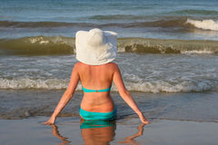 Girl sitting on the beach. With hat Royalty Free Stock Photo