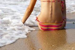 Girl sitting on the beach Stock Image