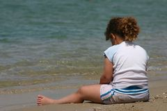 A Girl sitting on the beach. With her back to the camera, and playing in the sand Royalty Free Stock Photos