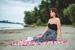 Girl sitting on the beach alone and looking far away. On a cloudy day Stock Images