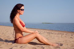 Girl sitting on the beach. Beatiful girl with black glasses sitting on the beach stock photos