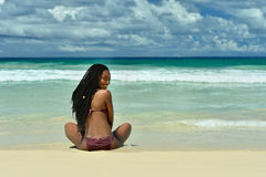 Girl sitting on the beach Stock Photography