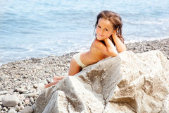 Girl sitting on the beach Stock Image