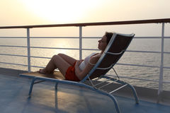 Girl sitting on beach chair at ship deck Stock Photos