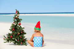 Girl Sitting On Beach With Christmas Tree And Hat Stock Image