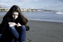 Girl sitting on the beach feeling cold and scared wide shot Stock Photos