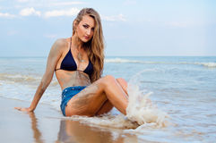 Girl sitting on the beach. Girl with long hair sitting on the beach. Wave splashed on her legs Royalty Free Stock Image