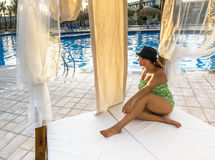 Girl sitting on a Beach Lounge Chair at the pool Royalty Free Stock Photography