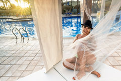Girl sitting on a Beach Lounge Chair at the pool Royalty Free Stock Images