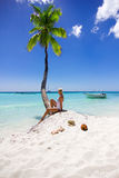 Girl sitting on the beach near palm tree Stock Photo
