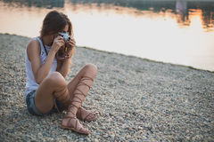 Girl sitting on the beach and photographing. Sunset royalty free stock image