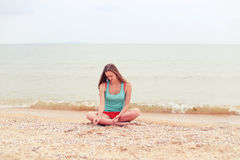 A girl sitting on the beach and playing with sand Royalty Free Stock Image
