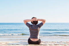 The girl is sitting on the beach practicing yoga. Stock Photography