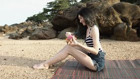 A girl sitting on the beach by the sea cuts a dragon fruit Pitaya. stock footage