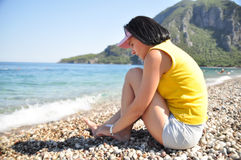 Girl sitting on the beach on the shingle Stock Photography