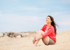 Girl sitting on the beach Stock Images