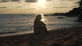 Girl sitting on the beach at sunset.  stock footage