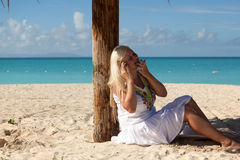 Girl sitting on the beach and talking on the phone Royalty Free Stock Photos